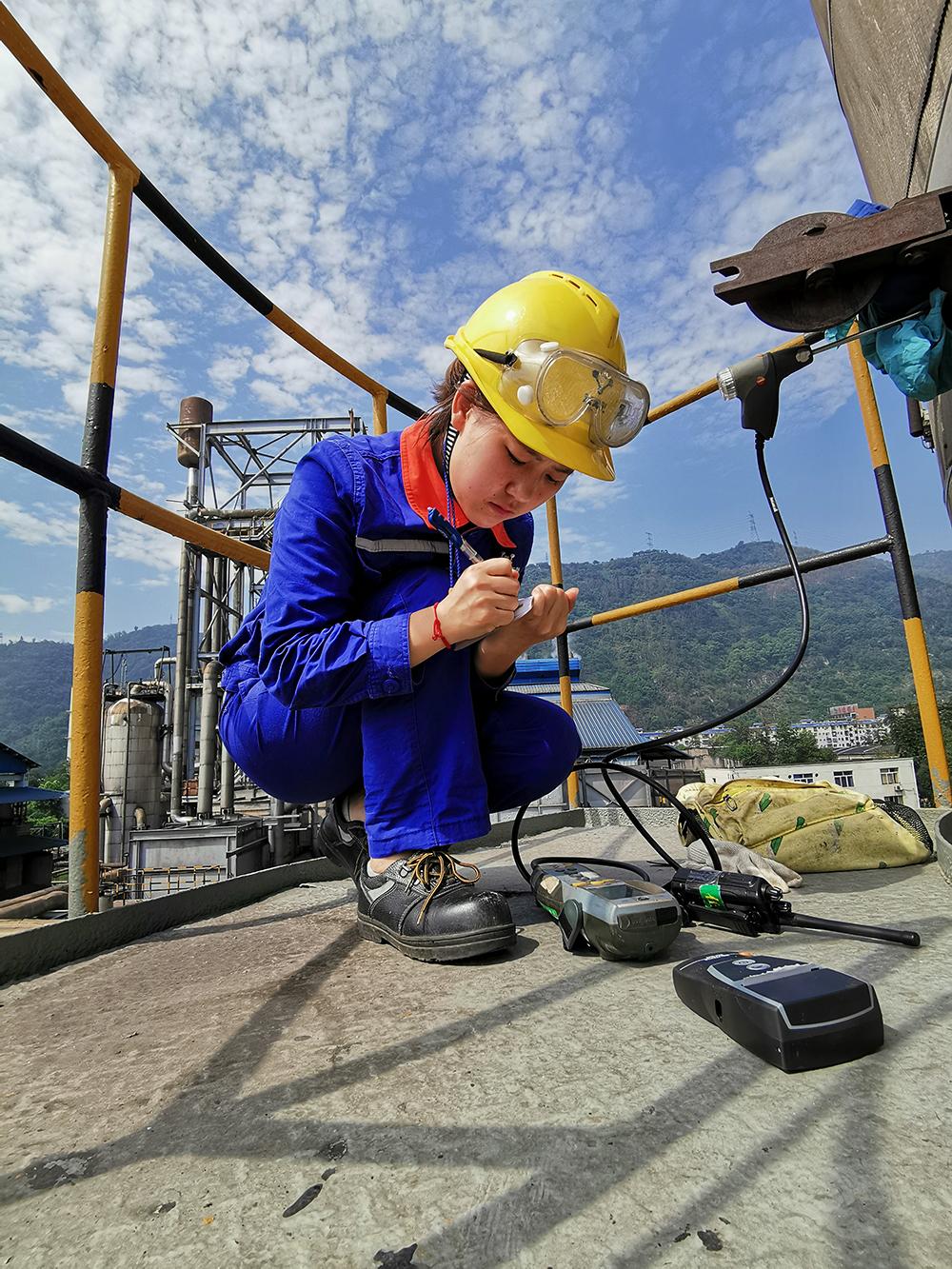 """蓝天下的""""环保卫士""""——作品说明:水富yabo88亚博体育app生产管理部一名女职工在高塔上做分析检测,在烈日下认真做好分析记录"""