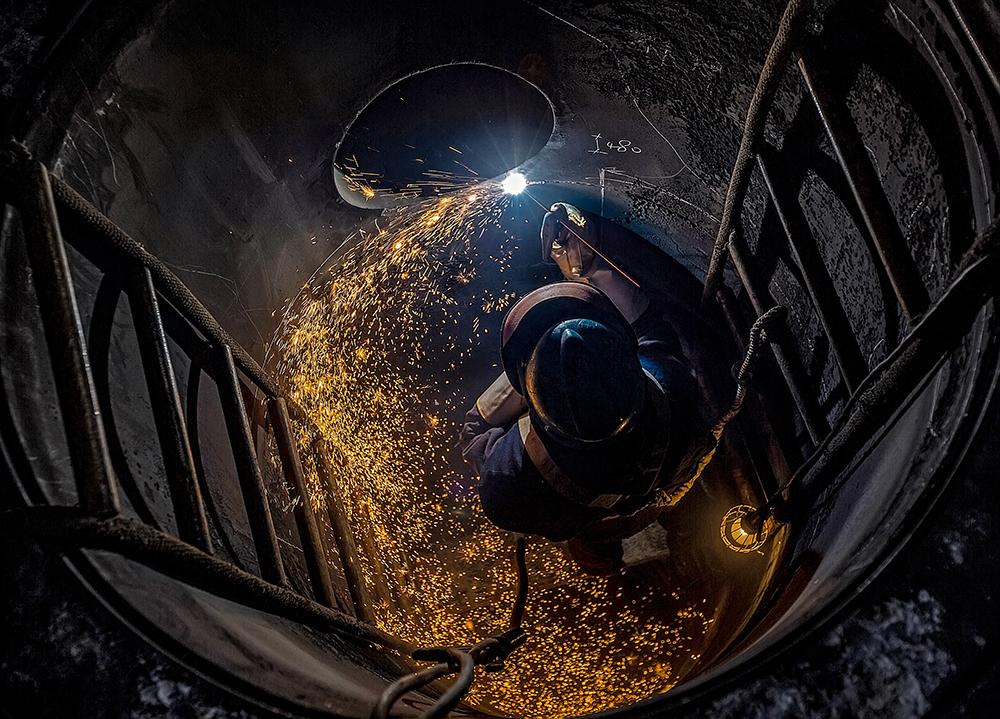 """《""""井""""上添花》作品说明:这是水富博猫1分彩博猫游戏维保事业部的一名焊工师傅在罐子内部作业的场景,焊花飞舞,照亮了整个设备"""
